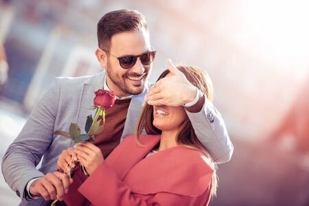 Handsome man giving red rose to his surprised girlfriend.Holidays,love,romance and people concept.