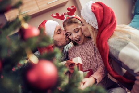 Beautiful family in Christmas interior.Happy parents kissing daughter and giving xmas present. Banque d'images - 129978270
