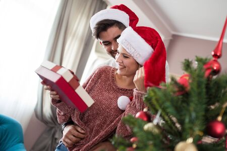 Romantic couple exchanging Christmas gifts at home.
