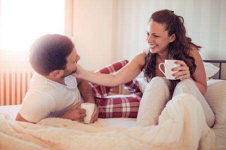 Cute happy couple in love huging in bed in their pijamas.