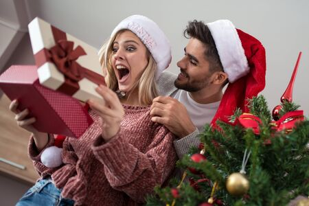 Romantic couple exchanging Christmas gifts at home. Banque d'images - 129978298