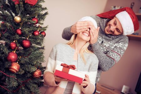 Happy young couple celebrating at home.Handsome man is giving his girlfriend a gift box.