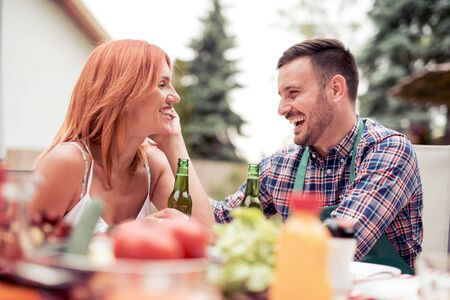 Couple in love enjoying their free time, making barbecue and having lunch in nature. Banque d'images