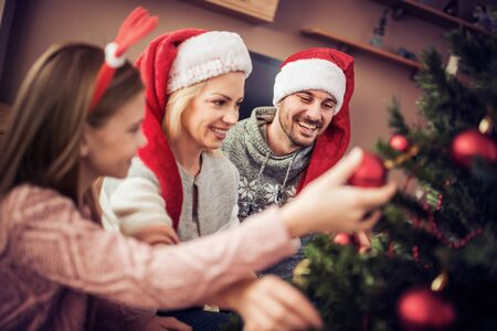 Happy young family decorating Christmas tree.Family, christmas, winter,happiness and people concept. Banque d'images