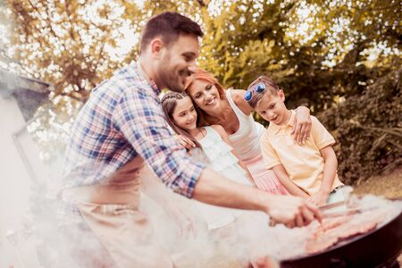 Happy family having a barbecue in their garden in summer.Leisure, food, family and holidays concept. Banque d'images - 129978315