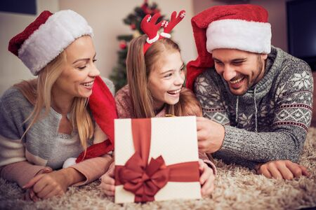 Young family on Christmas morning exchanging presents.Holidays, celebration, family and people concept. Banque d'images