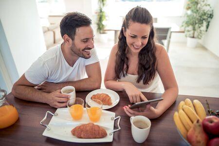 젊은 행복한 커플은 현대적인 아파트에 앉아서 함께 아침을 먹고 있습니다.