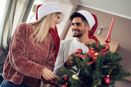 Happy couple decorating Christmas tree in their home. Banque d'images