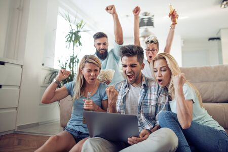 Group of friends watching sport together.Cheerful group of friends watching football game on laptop.