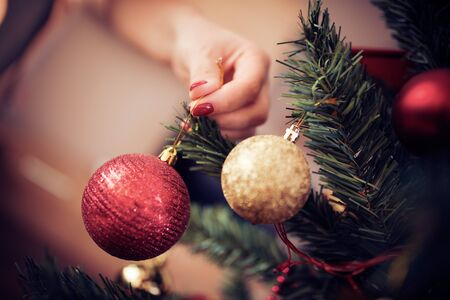 Close up of woman decorating christmas tree.Winter holidays,celebration and people concept.