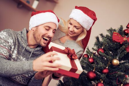 Surprise!Romantic young woman giving xmas present to her husband. Banque d'images - 129978344