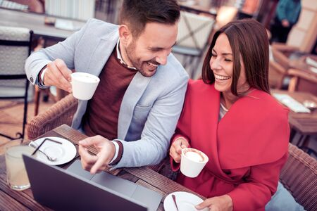 Beautiful young couple using laptop,talking and smiling while sitting in cafe. Banco de Imagens