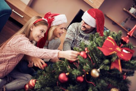 Merry Christmas and happy Holidays!Mother,father and daughter decorating christmas tree.