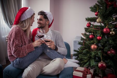 Happy young couple drinking red wine at home.Winter, couple, christmas and people concept. Banco de Imagens