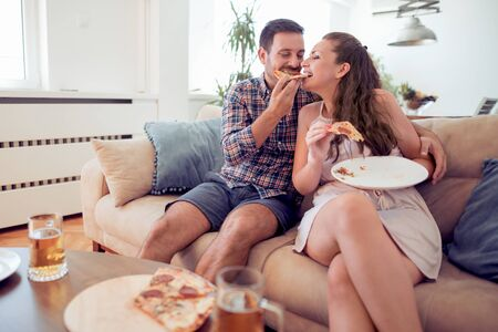 Couple eating pizza at home,having fun. Stock Photo