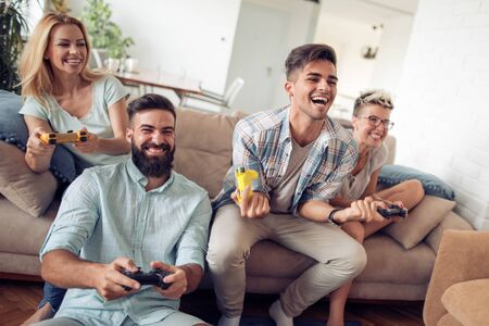 Beautiful couples playing video games on console,having fun together.