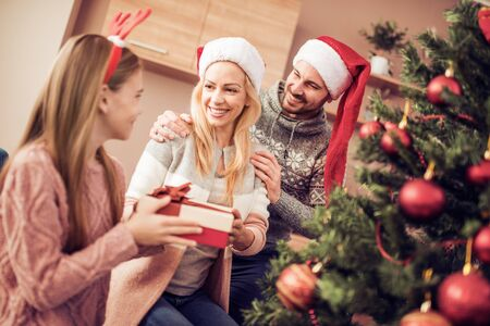 Young family on Christmas morning exchanging presents.Holidays, celebration, family and people concept. Banco de Imagens