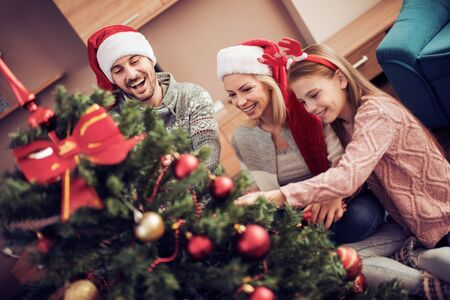 Merry Christmas and happy Holidays!Mom, dad and daughter decorating christmas tree.
