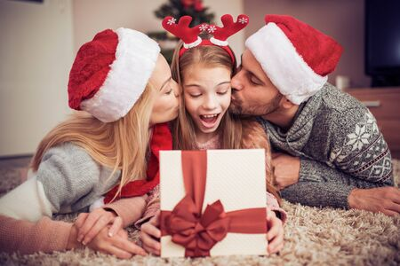 Beautiful family in Christmas interior.Happy parents kissing daughter and giving xmas present. Banco de Imagens