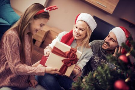 Happy family opening Christmas gift at home.Family, christmas, holidays and people concept. Banco de Imagens
