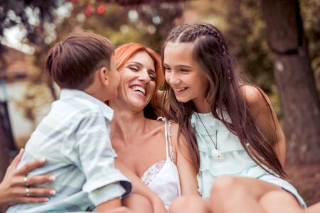 Cute smiling girl and boy give a present to their happy mother .They are kissing and embraced mom. Banque d'images - 129978403