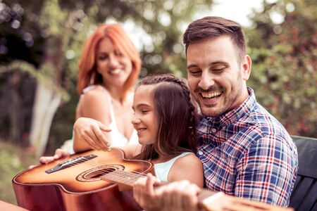 Young family enjoying quality time, playing guitar in their garden.