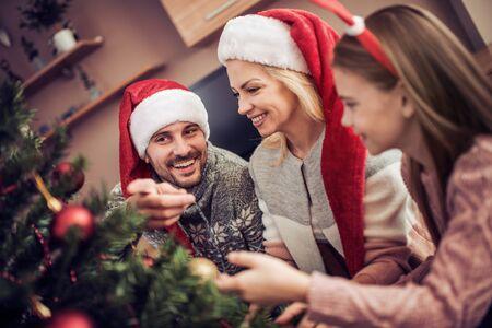 Jeune fille aidant à décorer le sapin de Noël. Concept de famille, Noël, Noël, bonheur et personnes.