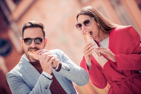 Couple eating sandwich and talking outdoor,having fun together. Banco de Imagens