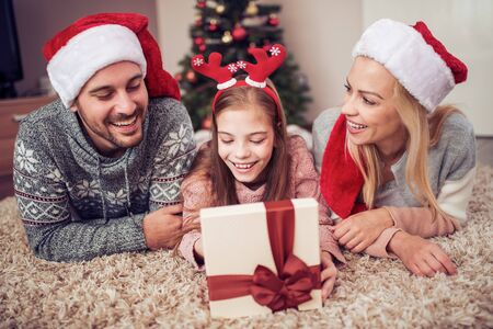 Family opening Christmas presents at home together.Family, christmas, winter, happiness and people concept. Banco de Imagens