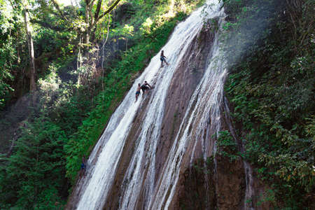 Dominicans jump into a waterfall from a height