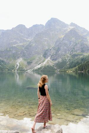 Girl in an elegant skirt on a background of clear lake and high mountains. Lake Morskie Oko, Tatra National Park, Poland Standard-Bild
