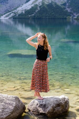 Portrait of a young smiling attractive girl in colorful clothes on sunny day on the lake and mountains background