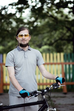 Portrait of handsome cyclist man standing outdoors in warm summer evening against colored fence and sunset background, looking into camera,wearing sunglasses