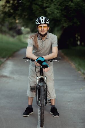 Portrait of man in a yellow sunglasses and helmet standing with bicycle on road and looking into camera