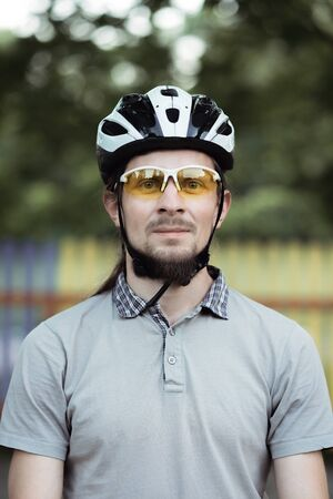 Close up shot of happy attractive young man with beard wearing protective helmet and yellow sunglasses looking at camera Фото со стока