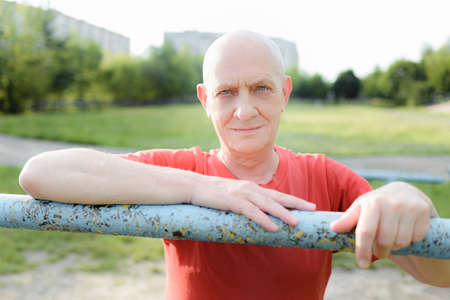 Portrait of middle aged sport man doing exercise in the park. Stock Photo
