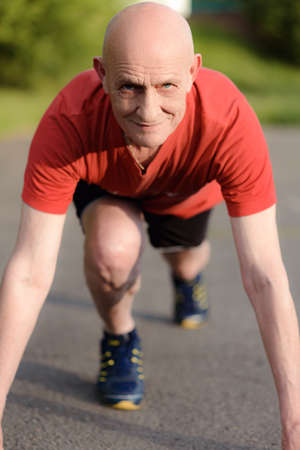 Senior man in position ready to run. Determined man ready for a sprint. Health lifestyle and Exercise Start Up Concept