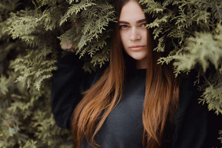 A beautiful young girl is standing on a background of green grass. Thuja tree