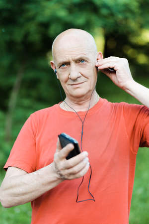 Photo of retired pensioner is wearing headphones while listening to music and trying to overhear in the park Stock Photo