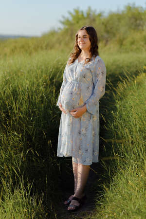 Side view of pregnant woman posing at sunset. Pregnant woman touching gently her tummy.