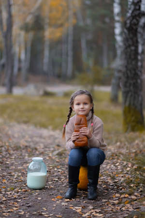 The girl sits on a pumpkin and holding a loaf of bread, and milk standing nearby