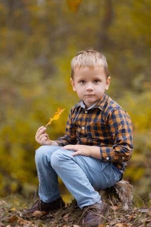 Little boy holding an oak leaf in his hands