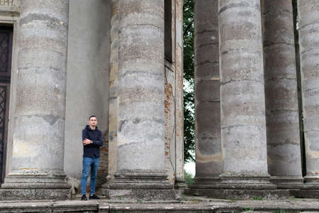 A man outsized by huge pillars of an ancient structure.