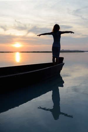 Silhouette of a girl on a boat on a background of sunset