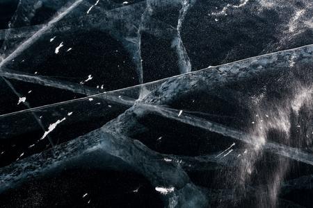 cracks in ice: Cracks on black transparent ice. The Baikal lake. Russia Stock Photo