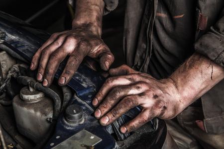 manos sucias: hombres que trabajan con las manos sucias se quedan cerca del motor de coche