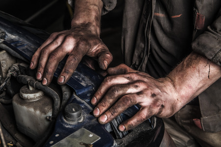 Working men with dirty hands stay near car engine