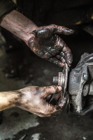 manos sucias: hombres que trabajan con las manos sucias y parte del coche Foto de archivo