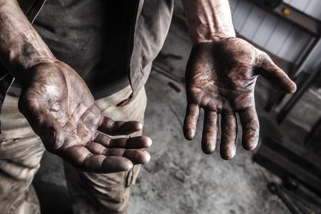 Las manos sucias de mecánico en la estación de coche Foto de archivo