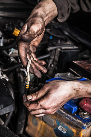 dirty man: Dirty man hands with oil gage and battery